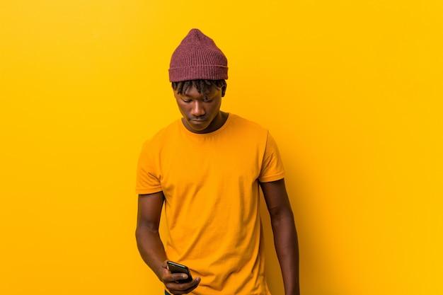 Junger afrikanischer mann, der gegen ein gelb trägt einen hut und verwendet ein telefon steht Premium Fotos