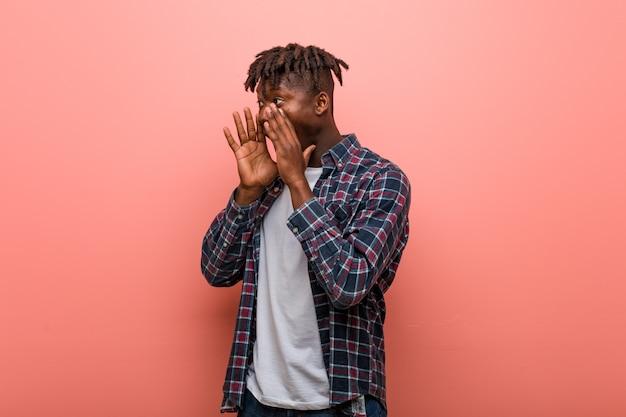 Junger afrikanischer schwarzer mann schreit laut, hält die augen offen und die hände angespannt. Premium Fotos