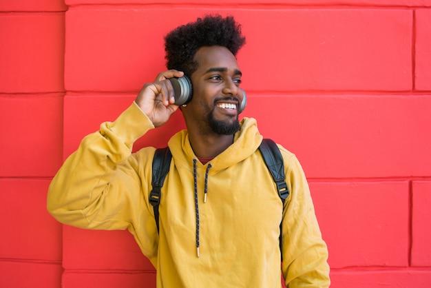 Junger afro-mann, der musik mit kopfhörern hört. Kostenlose Fotos
