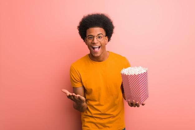 Junger afroamerikaner, der einen popcorneimer überrascht und entsetzt hält Premium Fotos