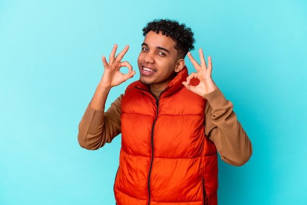 Junger afroamerikaner lockiger mann lokalisiert auf blau fröhlich und zuversichtlich zeigt ok geste. Premium Fotos