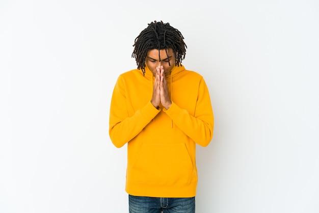 Junger afroamerikaner-rasta-mann, der betet und hingabe zeigt, religiöse person, die nach göttlicher inspiration sucht. Premium Fotos