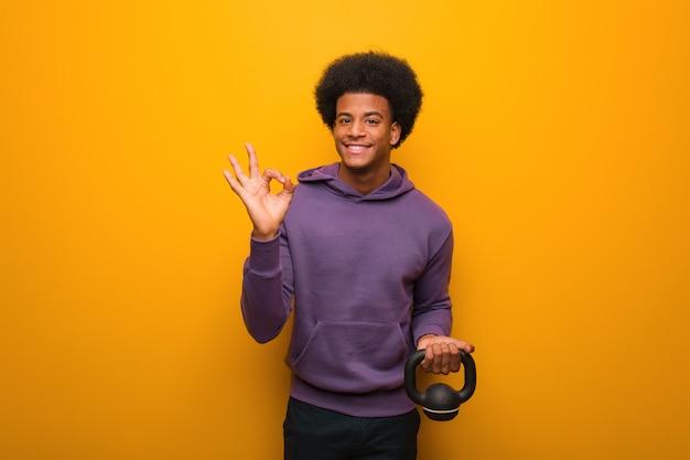 Junger afroamerikanereignungsmann, der einen dummkopf nett und überzeugt hält, okaygeste tuend Premium Fotos