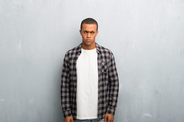 Junger afroamerikanermann mit dem karierten hemdgefühl gestört Premium Fotos