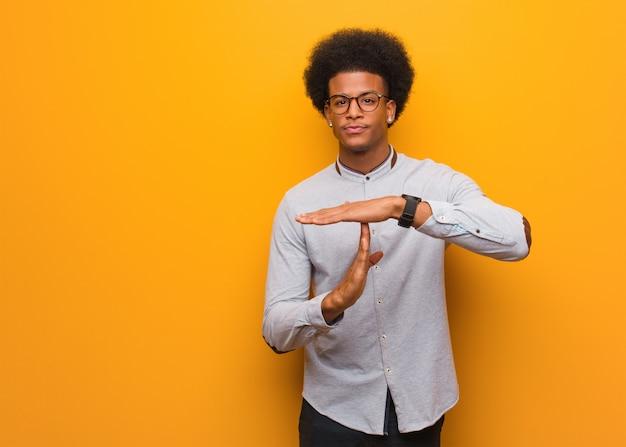 Junger afroamerikanermann über einer orange wand, die eine auszeitgeste tut Premium Fotos