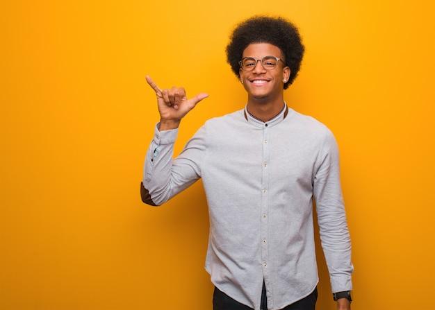 Junger afroamerikanermann über einer orange wand, die eine felsengeste tut Premium Fotos