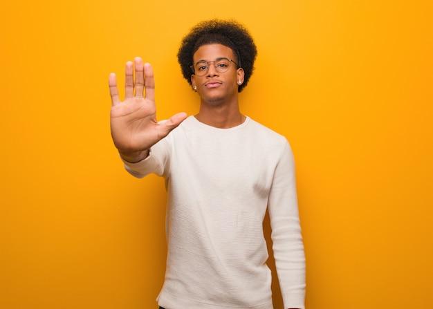 Junger afroamerikanermann über einer orange wand, die hand in front einsetzt Premium Fotos