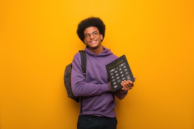 Junger afroamerikanerstudentenmann, der einen taschenrechner lächelt überzeugt und die arme kreuzt und oben schaut hält Premium Fotos