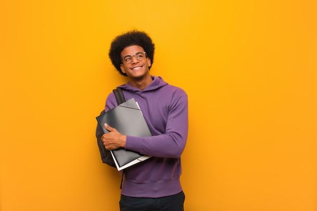 Junger afroamerikanerstudentenmann, der überzeugt lächelt und die arme, oben schauend kreuzt Premium Fotos