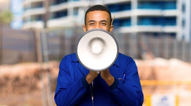 Junger afroamerikanischer arbeitskraftmann, der durch ein megaphon schreit, um etwas in einer baustelle anzukündigen Premium Fotos