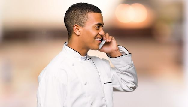Junger afroamerikanischer chefmann, der ein gespräch mit dem handy auf unfocused wand hält Premium Fotos