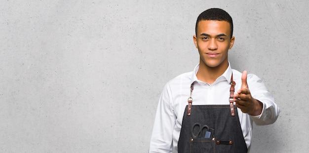 Junger afroamerikanischer friseurmann, der hände für das schließen eines abkommens auf strukturierter wand rüttelt Premium Fotos
