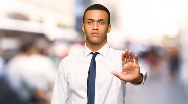 Junger afroamerikanischer geschäftsmann, der endgeste macht, eine situation zu leugnen, die in der stadt falsch denkt Premium Fotos