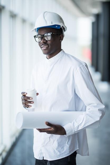 Junger afroamerikanischer ingenieur mit blaupausen vor panoramafenstern im büro Kostenlose Fotos