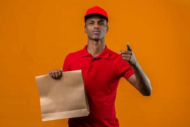 Junger afroamerikanischer lieferbote, der rotes poloshirt und kappe hält, die papiertüte mit essen zum mitnehmen zeigt, das mit finger auf kamera mit ernstem gesicht über isoliertem orange zeigt Kostenlose Fotos