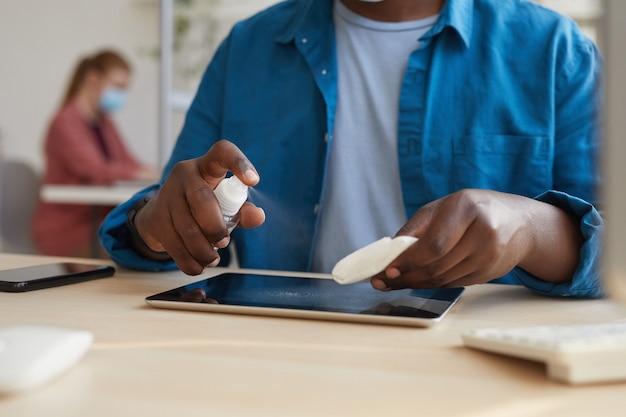 Junger afroamerikanischer mann, der tablette mit desinfektionstüchern abwischt, während er am schreibtisch im büro nach der pandemie arbeitet Premium Fotos