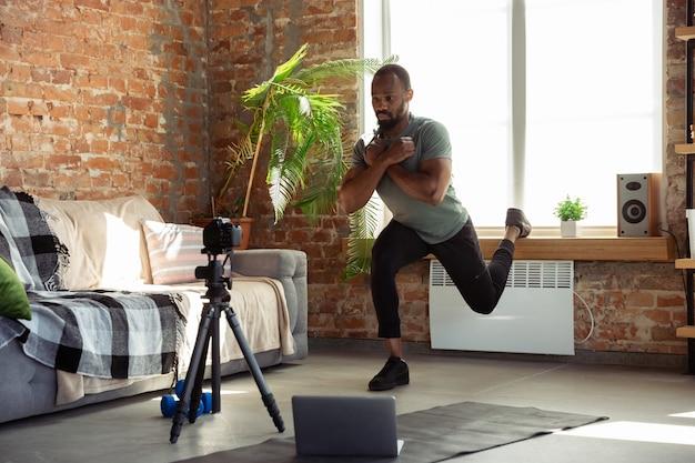 Junger afroamerikanischer mann, der zu hause online-kurse von fitness, aerobic, sportlichem lebensstil während der quarantäne, neuaufnahme vor der kamera, streaming unterrichtet Kostenlose Fotos