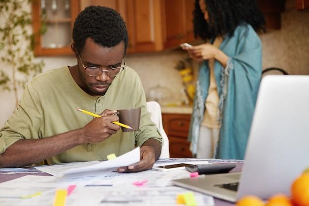 Junger afroamerikanischer mann in den gläsern, die kaffee trinken, beschäftigt, durch finanzen zu arbeiten Kostenlose Fotos