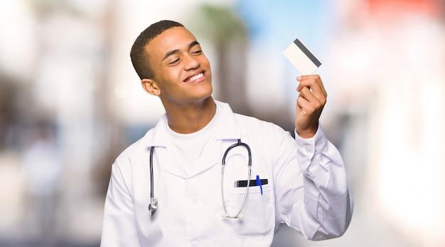 Junger afroamerikanischer manndoktor, der eine kreditkarte hält und an draußen denkt Premium Fotos