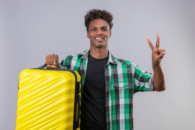 Junger afroamerikanischer reisender mann, der koffer hält, der kamera betrachtet, die fröhlich positiv und glücklich zeigt, nummer zwei oder siegeszeichen über weißem hintergrund zeigend Kostenlose Fotos