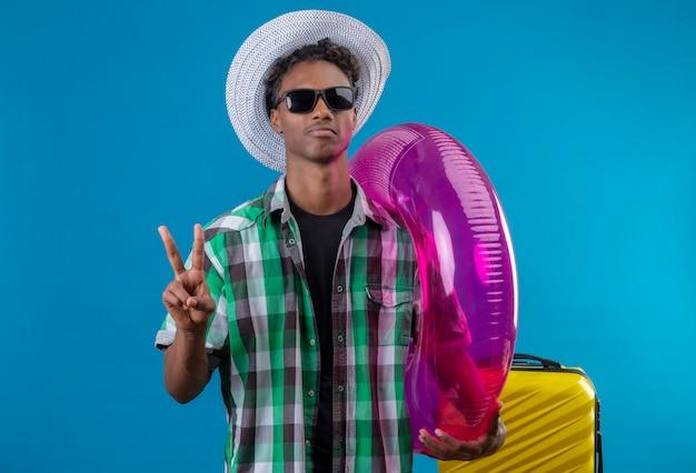 Junger afroamerikanischer reisender mann im sommerhut, der schwarze sonnenbrille mit koffer hält aufblasbaren ring, der nummer zwei oder siegeszeichen mit ernstem gesicht zeigt Kostenlose Fotos