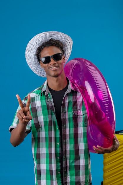 Junger afroamerikanischer reisender mann im sommerhut, der schwarze sonnenbrille steht, die mit koffer hält, der aufblasbaren ring hält, der nummer zwei oder siegeszeichen betrachtet, das die kamera lächelt, die fröhlich lächelt Kostenlose Fotos