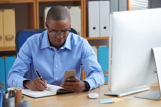 Junger afroamerikanischer unternehmer, der den tag plant Kostenlose Fotos