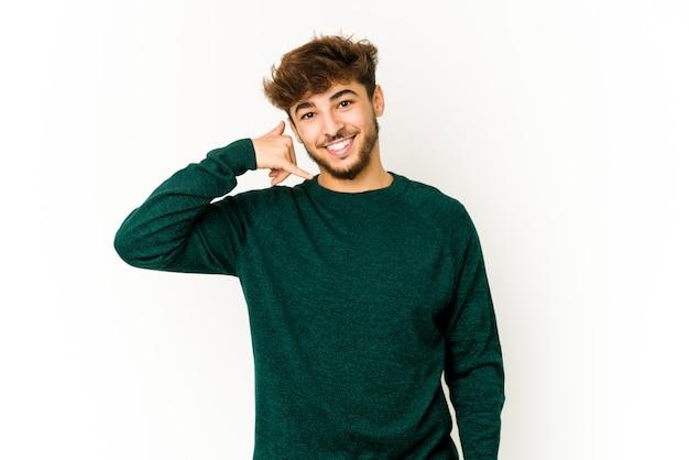 Junger arabischer mann auf weiß, der eine handy-anrufgeste mit den fingern zeigt. Premium Fotos