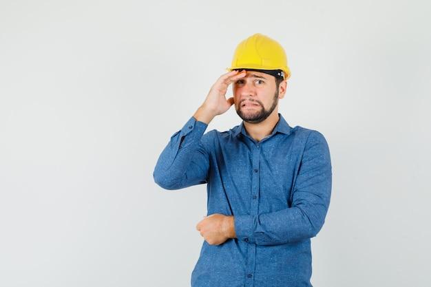 Junger arbeiter im hemd, helm, der hand über gesicht hält und verlegen aussieht Kostenlose Fotos