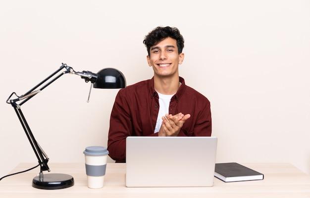 Junger argentinischer mann in einer tabelle mit einem laptop an seinem arbeitsplatz applaudierend Premium Fotos