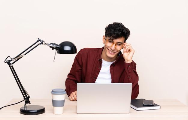 Junger argentinischer mann in einer tabelle mit einem laptop an seinem arbeitsplatz Premium Fotos