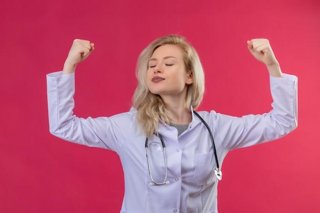 Junger arzt, der stethoskop im medizinischen kleid trägt und starke geste auf rotem hintergrund tut Kostenlose Fotos