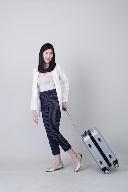 Junger asiatintourist mit dem gepäck zu reisen Premium Fotos
