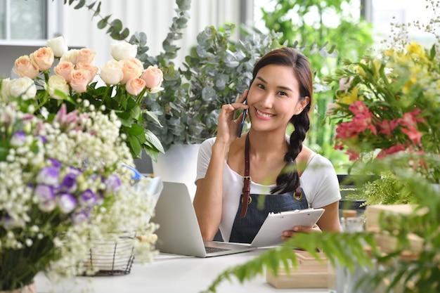 Junger asiatinunternehmer / ladenbesitzer / florist eines kleinen blumenladengeschäfts Premium Fotos