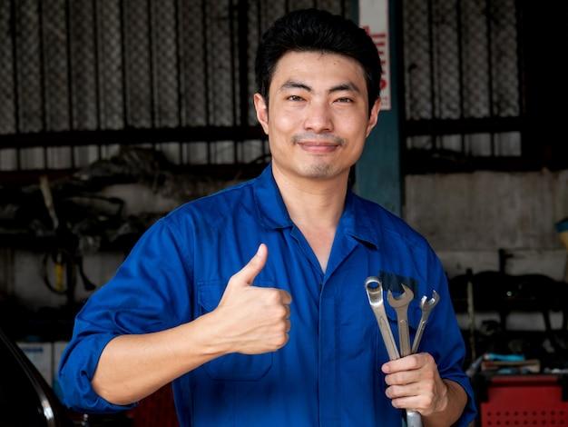 Junger asiatischer automechaniker in der uniform, die schlüssel hält und daumen oben in der garage zeigt. Premium Fotos