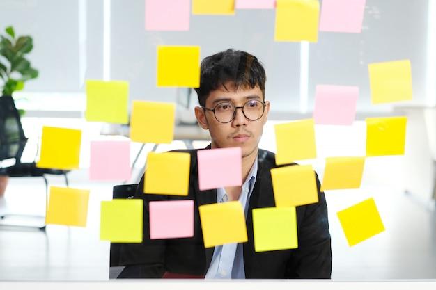 Junger asiatischer denkender geschäftsmann beim ablesen von klebrigen anmerkungen im büro, geschäft, das kreative planierungsideen zum erfolg im geschäft brainstroming ist Premium Fotos