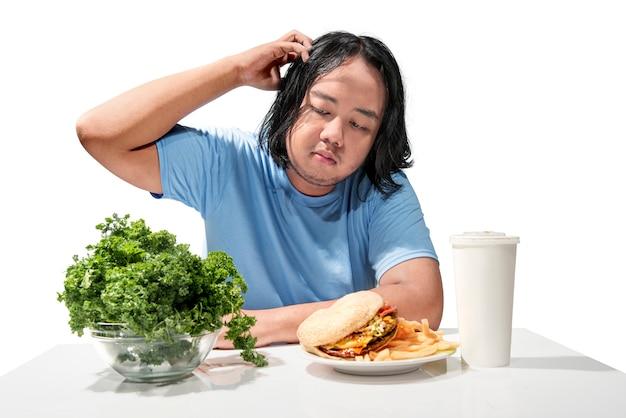 Junger asiatischer dicker mann verwirrte das wählen zwischen schnellimbiß oder gesundem lebensmittel Premium Fotos