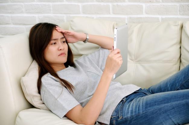 Junger asiatischer frauenkampf mit digitaler tablette, das frustrierte asiatische mädchen, das digitale tablette beim lügen auf sofa, leute betrachtet, kämpfen mit technologie Premium Fotos