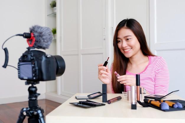 Junger asiatischer frauenschönheit blogger, der kosmetik beim aufzeichnen zeigt, wie man videotutorial durch kamera bildet Premium Fotos
