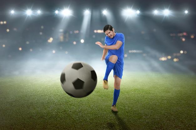 Junger asiatischer fußballspieler, der die kugel schießt Premium Fotos
