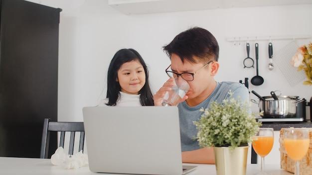 Junger asiatischer geschäftsmann ernst, druck, müde und krank beim an laptop zu hause arbeiten. junge tochter, die ihren vater tröstet, der morgens schwer in der modernen küche am haus arbeitet. Kostenlose Fotos