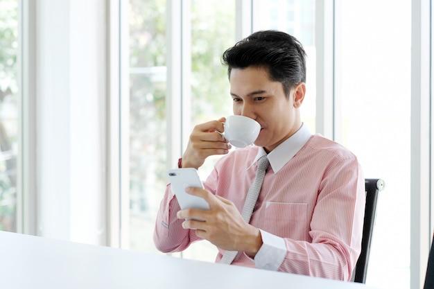 Junger asiatischer geschäftsmann unter verwendung des intelligenten telefons und des trinkenden kaffees im büro Premium Fotos