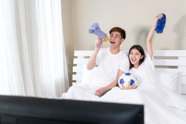 Junger asiatischer hübscher ehemann und schöne frau fühlen sich großartig, wenn sie ihrem team zujubeln Kostenlose Fotos
