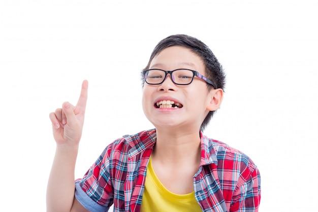 Junger asiatischer junge, der oben zeigt und über weißem hintergrund lächelt Premium Fotos
