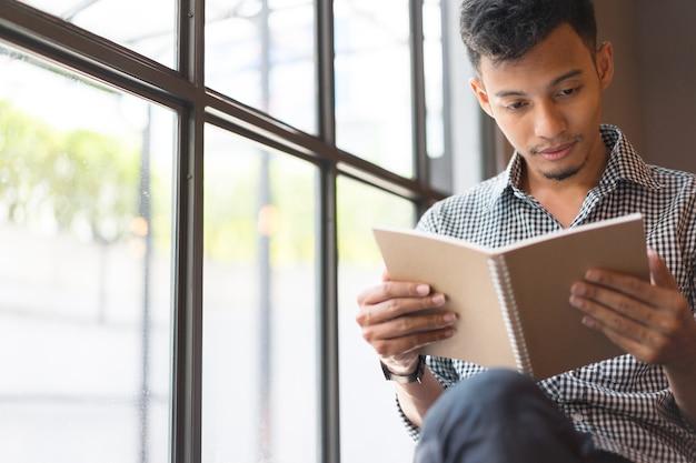 Junger asiatischer mann, der ein kleines buch am kaffeekaffeeshop liest Premium Fotos