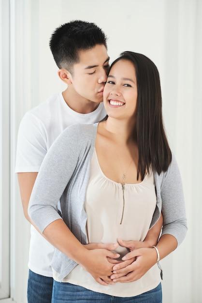 Junger asiatischer mann, der freundin auf backe umarmt und küsst Kostenlose Fotos