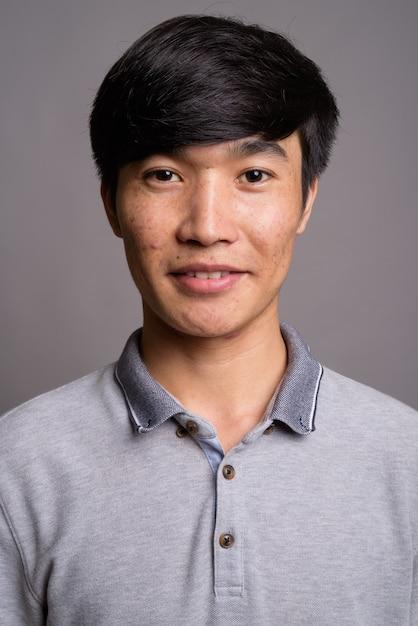 Junger asiatischer mann, der graues poloshirt gegen graue wand trägt Premium Fotos