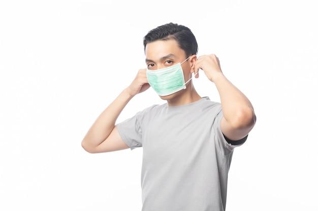 Junger asiatischer mann, der hygienemaske trägt, um infektion, 2019-ncov oder coronavirus zu verhindern. atemwegserkrankungen in der luft wie pm 2.5-kämpfe und grippe. studioaufnahme isoliert Premium Fotos