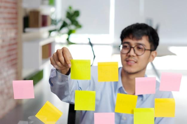Junger asiatischer mann, der klebrige anmerkung über glaswand im büro, geschäft gedanklich löst kreative ideen, bürolebensstil, erfolg im geschäft liest Premium Fotos