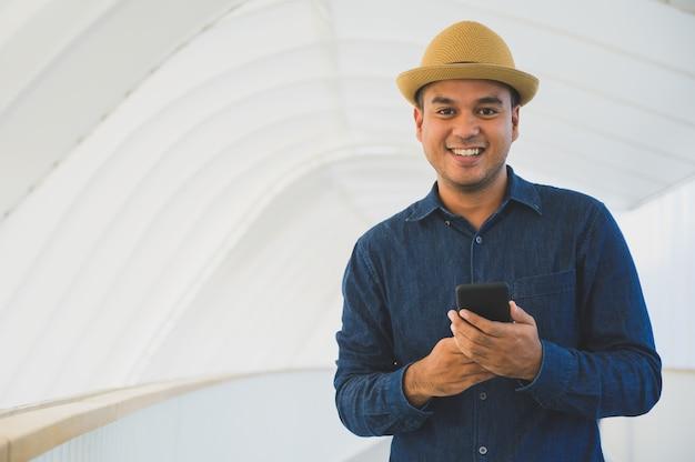 Junger asiatischer mann, der smartphone verwendet. Premium Fotos